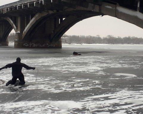 В Киеве с моста в Днепр упал мужчина: фото и видео, как его доставали