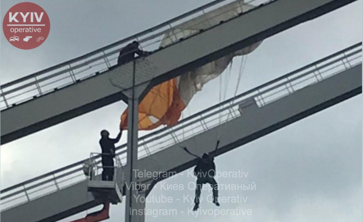 Парашутист повис на пішохідному мосту в Києві